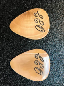 Custom designed and engraved guitar picks made from fossilized woolly mammoth tusks from Alaska